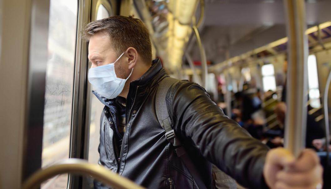 En person beskytter seg med maske på T-banen i New York under koronavirusutbruddet.
