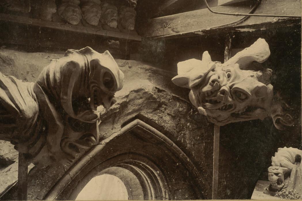Fra Vigelands første opphold i domkirken november-desember 1898 finnes kun noen få fotografier. På dette fotografiet fra Vigelands atelier ved skipets søndre vest-tårn ser vi figurer til hovedtårnet ferdig modellert i leire. Vigelands atelier var lite og uegnet til å modellere de store tårnskulpturene. For å kunne se vannspyerne i riktig perspektiv brukte Vigeland et speil som lå på gulvet under modelleringen.