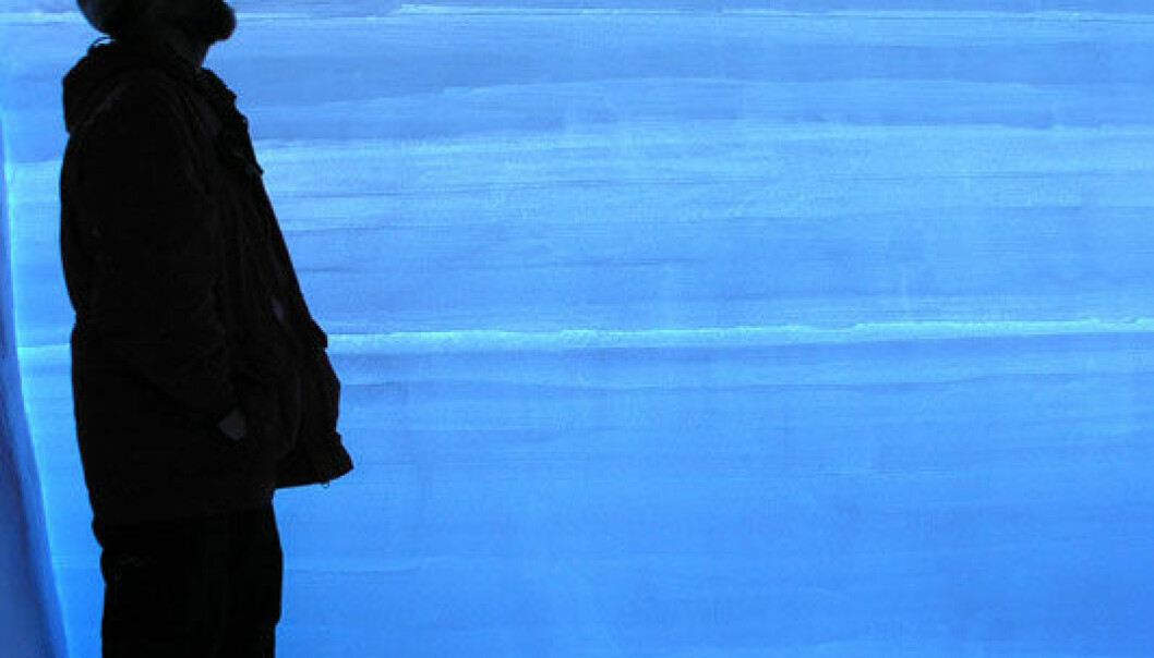 En forsker står ved siden av en iskjerne fra Vest-Antarktis. Hver av de horisontale strekene i iskjernen representere ett års snøfall. I alt dekker iskjernen 68 000 år klimahistorie. Kendrick Taylor/Desert Research Institute