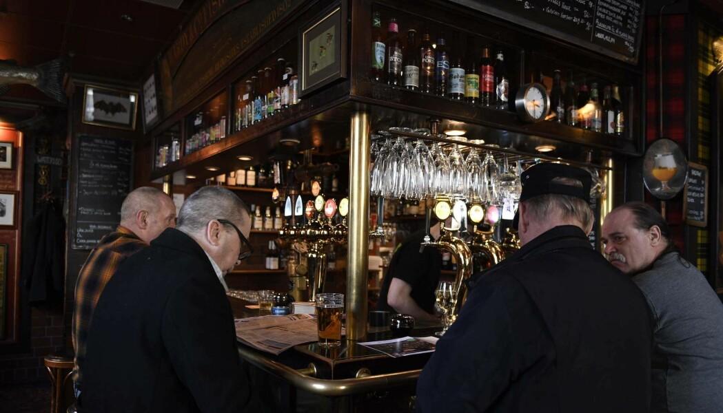 Menn drikker øl på bar i Stockholm 23. mars i år. Mens Oslos ølkraner var stengt, har restauranter og barer holdt åpent i Sverige til tross for koronakrisen.