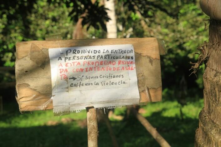 «Adgang forbudt for personer med voldelige intensjoner. Vi er kristne, og unngår vold», står det på plakaten ved en gård som fortsatt er eid av vanlige folk. Området i Honduras er tatt over av narkotikasmuglere. (Foto: Daniel Byers)