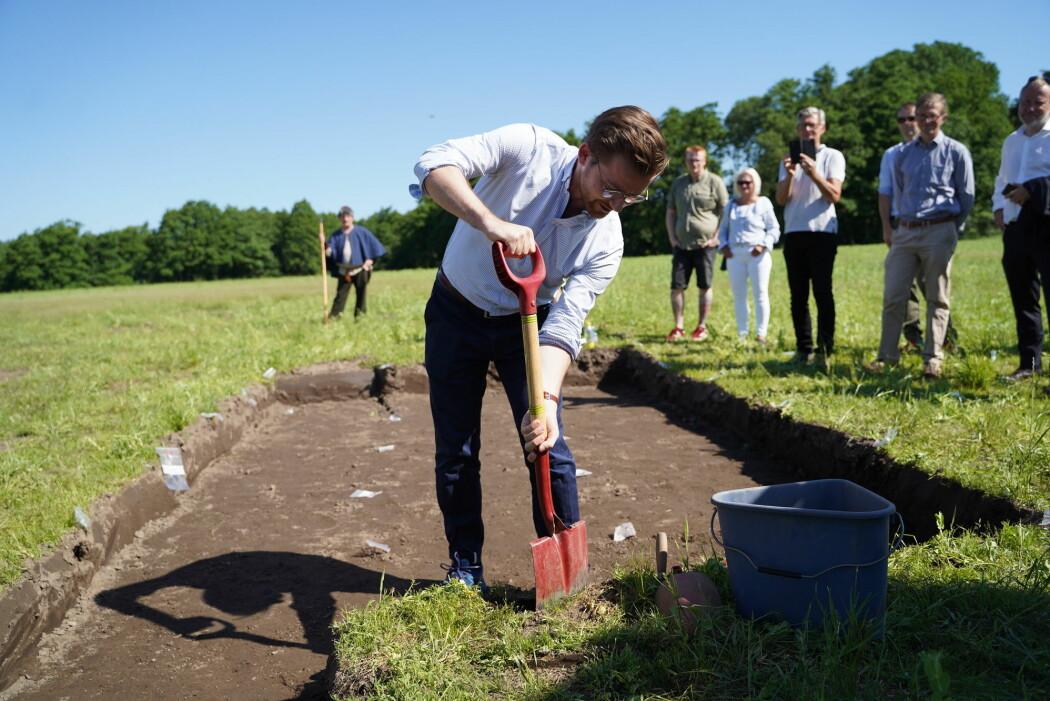 Klima- og miljøminister Sveinung Rotevatn tar første spadetak i utgravingen av Gjellestadskipet. Utgravingen er ventet å ta fem måneder, og det er første gang på over 100 år at et vikingskip blir gravd fram i Norge.