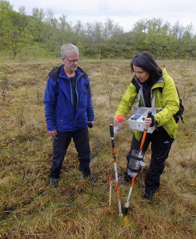 NGU-forsker Janja Knezevic Solberg viser fylkesgeolog Ola Torstensen i Nordland måleutstyret som blir brukt i grafittundersøkelser. Bildet er tatt ved Haugsnesdalen, Bø i Vesterålen.