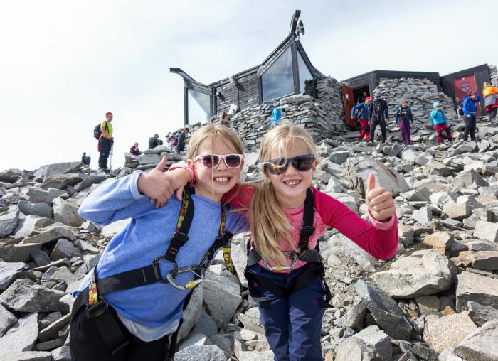 Å bestige Galdhøpiggen er noe flere nordmenn kanskje gjør i sommer. Her to jenter som var på toppen av Norges høyeste fjell sommeren for to år siden.