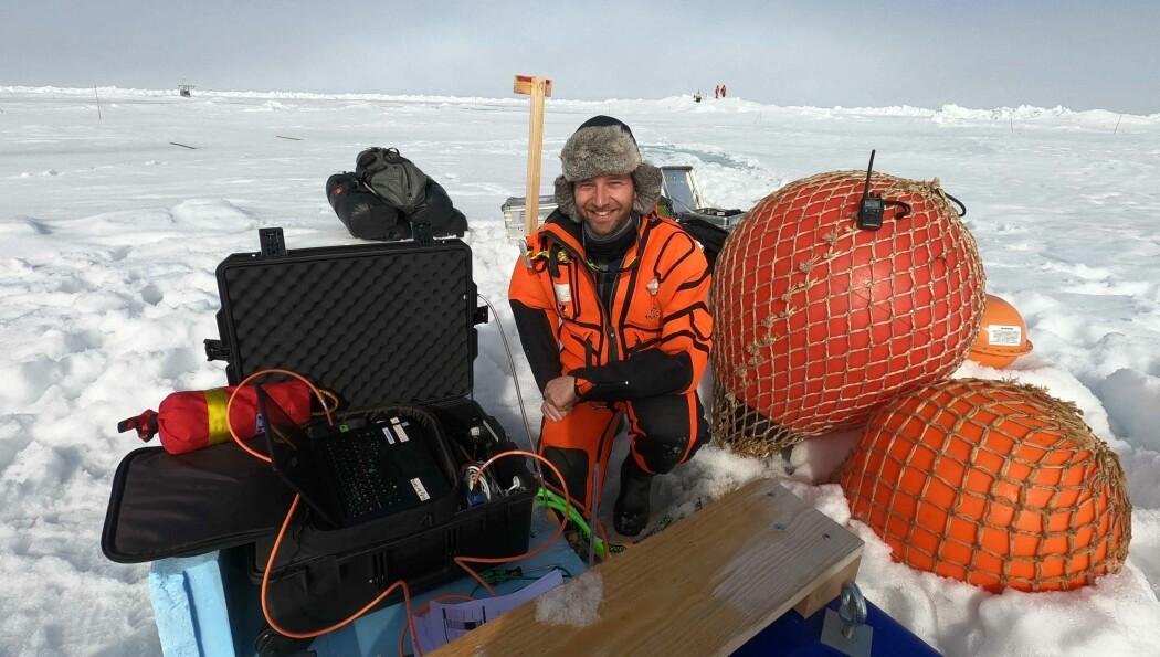 Morven Muilwijk ute på isen og laster ned data fra undervannsinstallasjoner