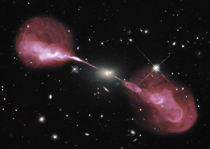 Radiogalaksen Hercules A. Selve galaksen ses i midten. Jetstrømmer og radio-lober strekker seg langt utenfor stjernenes utbredelse.