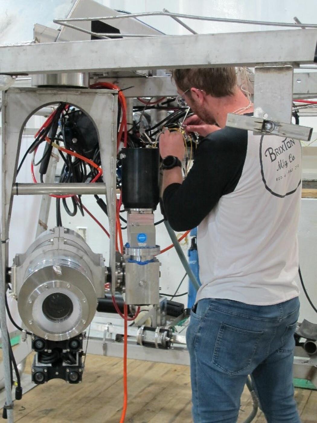 "Videoriggen ""Chimaera"" klargjøres, her ved instrumentingeniør Sindre Nygård Larsen. Nede til venstre ses riggens hovedkamera, bygd inn i en titankapsel som tåler flere tusen meters dyp. Foto: B. Holte"
