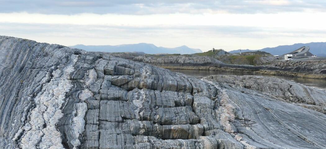 Den tydelige lagdelte strukturen vi ser i gneisene ble opprinnelig dannet dypt i jordskorpen. I bakgrunnen skimtes den renskårne veiskjæringen og det karakteriske sjømerket på Skipsholmen sammen med noen av Atlanterhavsveiens mange bruer.