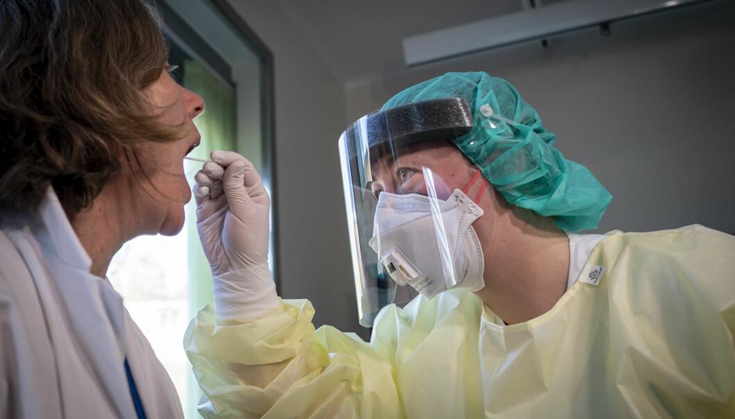 En fagutviklingssykepleier i fullt smittevernutstyr tar en spyttprøve på isolatposten på Ullevål sykehus. I starten av pandemien var det mangel på både smittevernutstyr og tester.