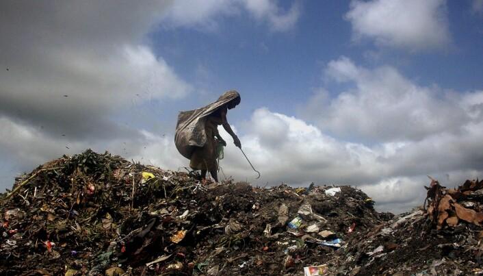 En kvinne samler plast som kan resirkuleres i India.