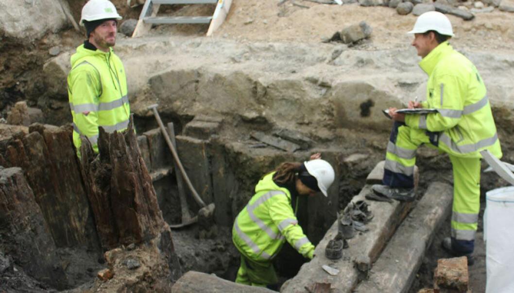 Her holder tre arkeologer på å grave ut en de mange kassene hvor de blant annet har funnet rester fra flere glassflasker. Anne Marie Lykkegaard