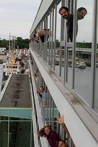 Forskarar i karantene kikker ut frå kvart sitt hotellrom