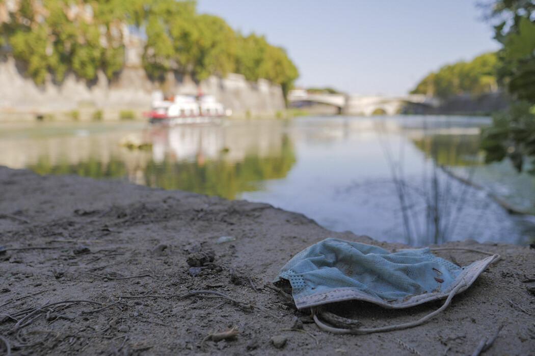 Et brukt munnbind ved bredden av elva Tiber i Roma.