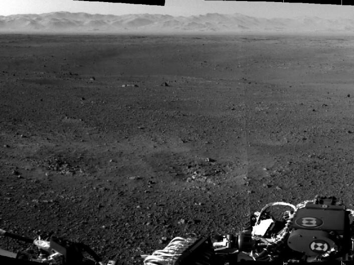 Dette er et av de første høyoppløselige bildene fra Mars-overflaten, tatt av et av navigasonskameraene på Curiosity. Blant annet kan kanten på Gale Crater ses i bakgrunnen, bortenfor den ellers småteinete overflaten. Samtidig ser vi mer i front av bildet avtrykk etter rakettene fra landingsfartøyet som hjalp Mars-roveren den siste biten ned til den røde planet. (Foto: NASA/JPL-Caltech)
