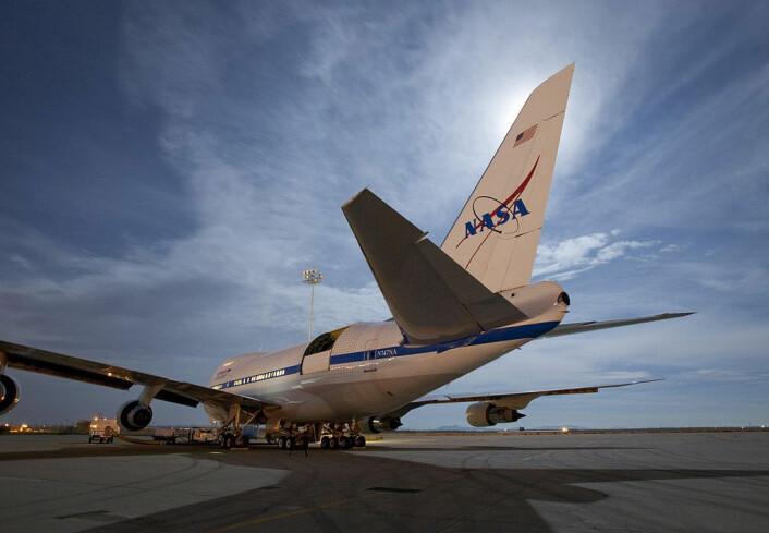 Stratospheric Observatory for Infrared Astronomy (SOFIA) er verdens største flybårne observatorium. Fra en lasteluke i en Boeing 747 ser det 2,5 meter store speilteleskopet i infrarødt lys mot fjerne stjernetåker. Lasteluken inn til teleskopet står åpen bak vingen. (Foto: NASA)