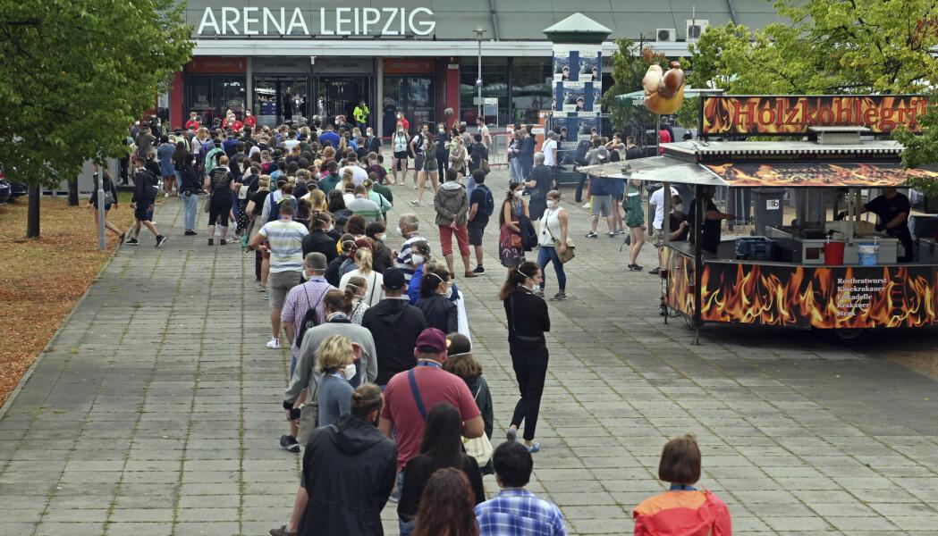 Konsertgjengere og forsøkskaniner står i kø utenfor en arena i Leipzig der de skal delta i et vitenskapelig forsøk som skal studere spredning av koronavirus i store forsamlinger innendørs.