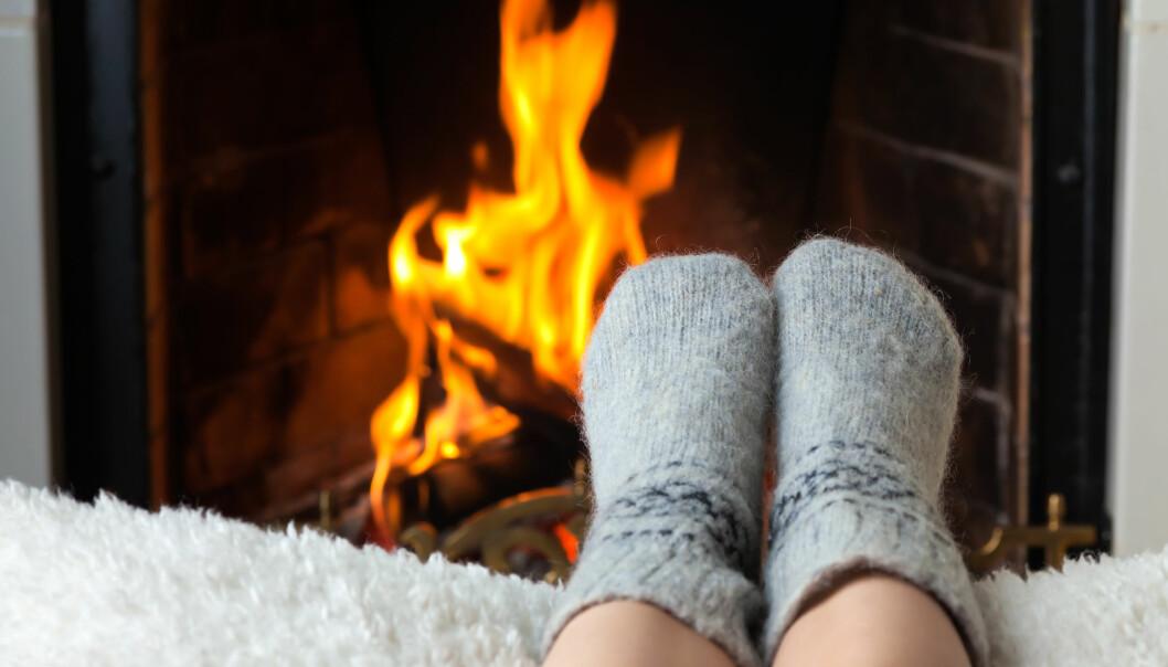 Children's feet in warm woolen socks heated in the fire in the fireplace