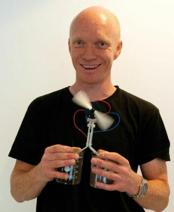 Ole Martin Løvvik demonstrerer termoelektrisitet med ett glass kaldt og ett glass varmt vann. Den nye teknologien utnytter temperaturforskjellen og gir energi til en hurtig roterende vifte. (Foto: Yngve Vogt)