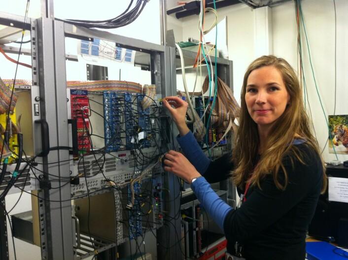 Forsker Ann Cecilie Larsen ved elektronikkboksene i datarommet på UiO. Her behandles signalene fra måleinstrumentene i eksperimenthallen. (Foto: Trine W. Hagen)