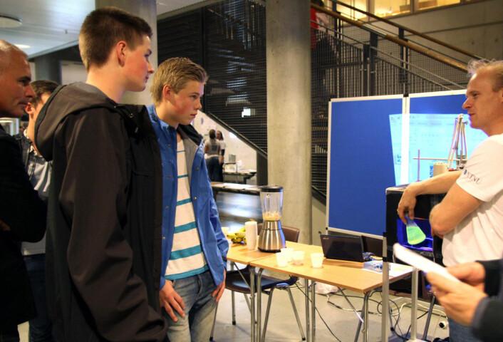 Kjemiprofessor Øyvind Mikkelsen forklarer bananens kjemiske egenskaper til Arvid Espen og Torbjørn Røising. (Foto: Kristina Jones, NTNU