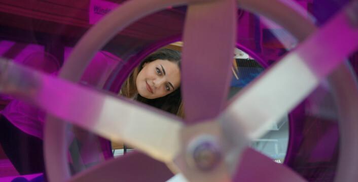 Nora Caroline Hansen sett gjennom en av propellene hun har vært med på å utvikle for firmaet WindDuct, som satser på vindkraftanlegg som kan monteres på småhustak. (Foto: Arnfinn Christensen, forskning.no.)