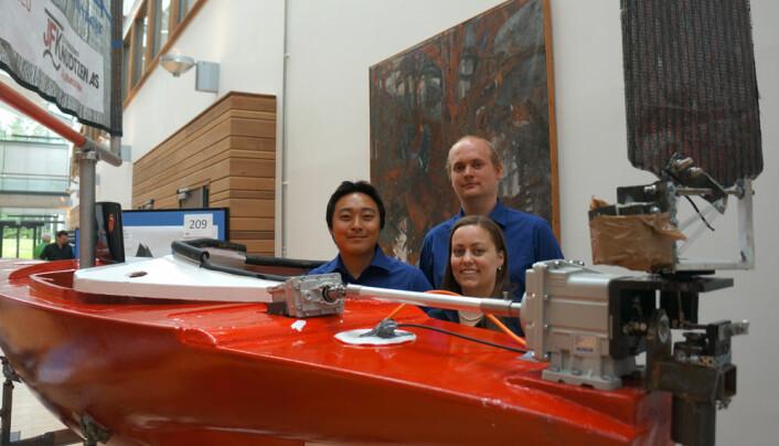 Tommy Lee Åsvang (t.v), Julie Venøy og Erlend Øksnes bak seilbåten Autonomus. Til høyre vindroret, som korrigerer for kastvinder. Det er koblet til et vindror, som igjen vrir hovedroret slik at båten kommer tilbake på kurs. (Foto: Arnfinn Christensen, forskning.no.)