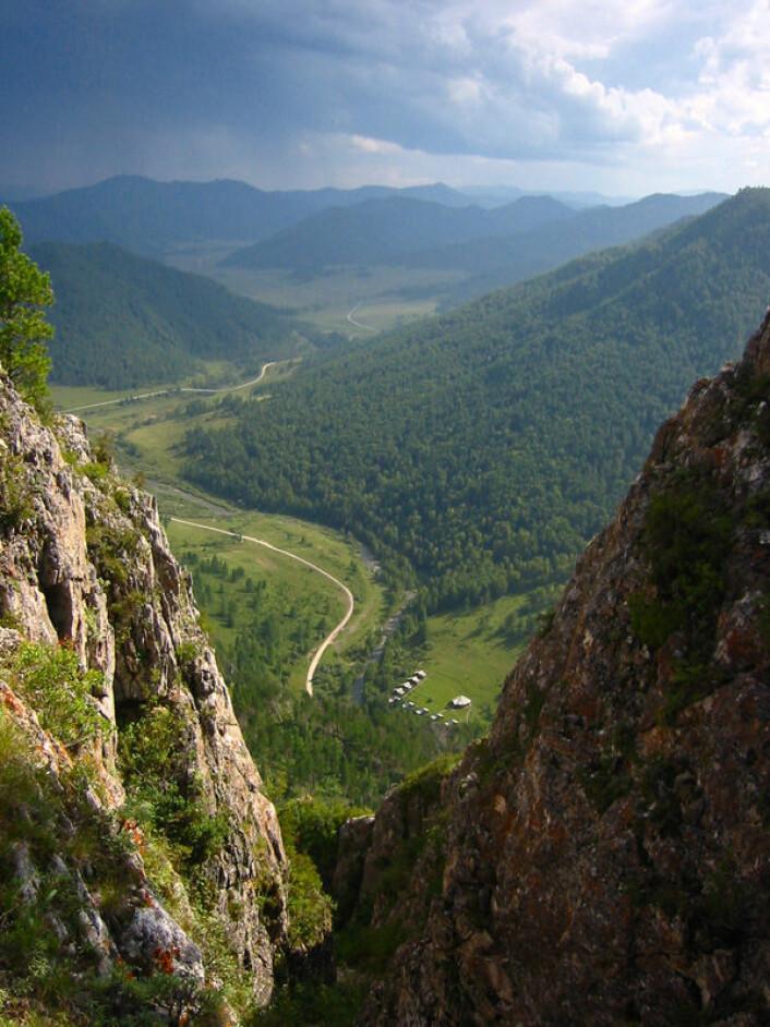 Utsikt fra høyde over Denisova-hulen. Dette landskapet i Altaj ved dagens landegrense mellom Russland, Kina og Mongolia kan ha vært denisovanernes siste tilholdssted. Teltleiren på bildet tilhører arkeologer som arbeidet i hulen. (Foto: Max Planck Institute for Evolutionary Anthropology)