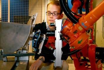 Lars Tingelstad ser til at alt er slik det skal vere med industriroboten han nyttar i sitt forskingsprosjekt. (Foto: Maria Gilje Torheim)
