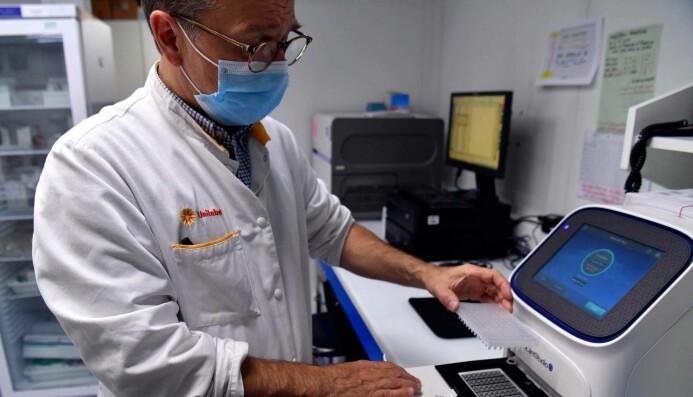 En PCR-maskinen er et lite varmeapparat som kan veksle mellom ulike temperaturer i syklus. Ved høye temperaturer vil DNA åpne seg som en glidelås. De som utfører testen, har puttet enzymer i prøvene som skal testes. Disse enzymene lager nye kopier av DNA. Da blir det dobbelt så mange «glidelåser» for hver syklus. Det er viktig at enzymene bare kopierer opp korona-arvestoffet. Derfor bruker helsearbeiderne små DNA-koder fra viruset. Disse små kodene fester seg til den åpne glidelåsen. Slik viser de vei så enzymet kan finne frem til korona-arvestoffet som skal kopieres opp.