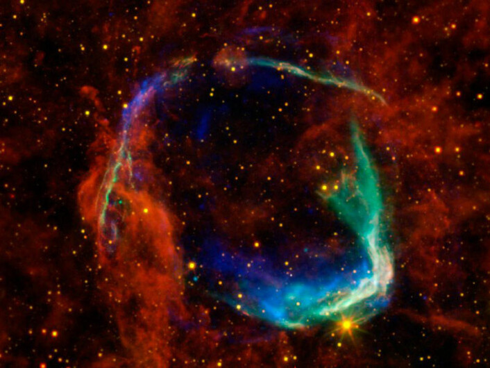 Restene av supernovaen fra 185 e.Kr, i en montasje av fotografier fra fire forskjellige romteleskop: De gule og røde delene er fra NASAs WISE-teleskop, og viser støv som stråler i infrarøde varmestråler. De blå og grønne delene viser røntgenstråler observert med det europeiske XMM-Newton-observatoriet og NASAs Chandra-observatorium. (Foto: ESA/NASA)