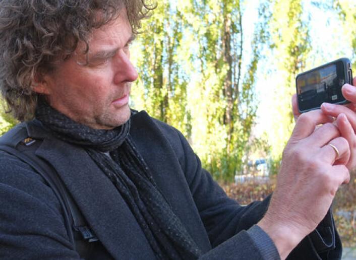 Professor Gunnar Liestøl demonstrerer hvordan du kan ta bilder av den virtuelle og den virkelige verden samtidig. (Foto: Norunn K. Torheim)
