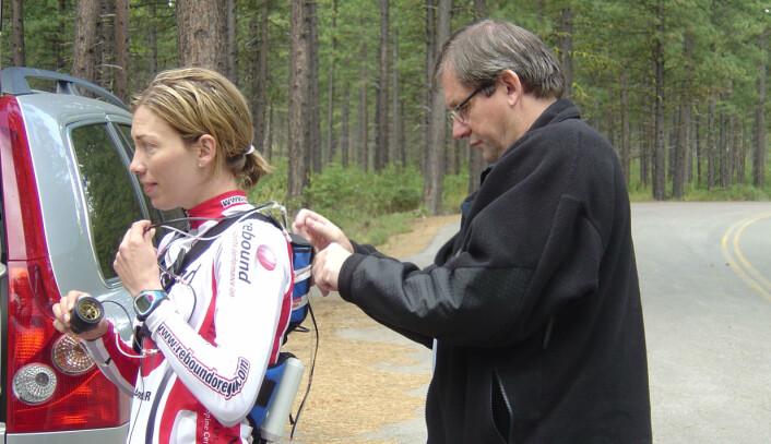 Her monterer professor Jan Helgerud bærbart utstyr for måling av oksygenopptak. Kvinnen på bildet er Beckie Scott, olympisk mester i langrenn fra Canada. Det som skulle testes her var maksimalt oksygenopptak på rulleski. (Foto: Privat)