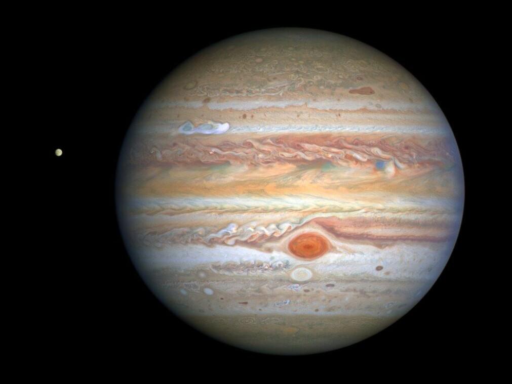Jupiter som vi kjenner den, med den karakteristiske røde flekken, en storm som er 2–3 ganger større enn jorden, samt en ny, hvit stormsky som er synlig i den øvre siden av planeten. Til venstre for Jupiter ser vi ismånen Europa.