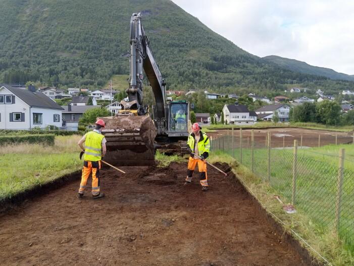 Slik har forskerne jobbet: en gravemaskin fjerner øverste jordlag. Bak følger forskerne som finkjemmer området, og alle funn kartlegges.