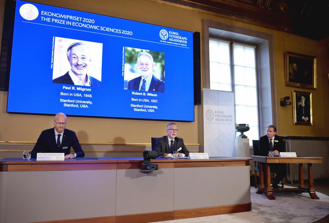 Generalsekretær Göran K. Hansson i Kungliga Vetenskapsakademien (t.h.) og priskomitéleder Peter Fredriksson presenterte mandag vinnerne av økonomiprisen. På skjermen bak dem er det bilde av prisvinnerne Paul R. Milgrom (t.v.) og Robert B. Wilson.