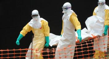 Doktorer fra Leger Uten Grenser bærer liket av en Ebola-rammet i Guekedou i Guinea. (Foto: AFP)