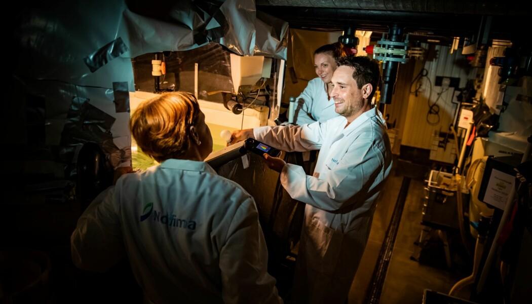 Jelena Kolarevic, med ryggen til, observerer fisk som blir lysstyrt sammen med forsker Andre Meriac og forskningstekniker May Britt Mørkedal hos Nofima på Sunndalsøra.