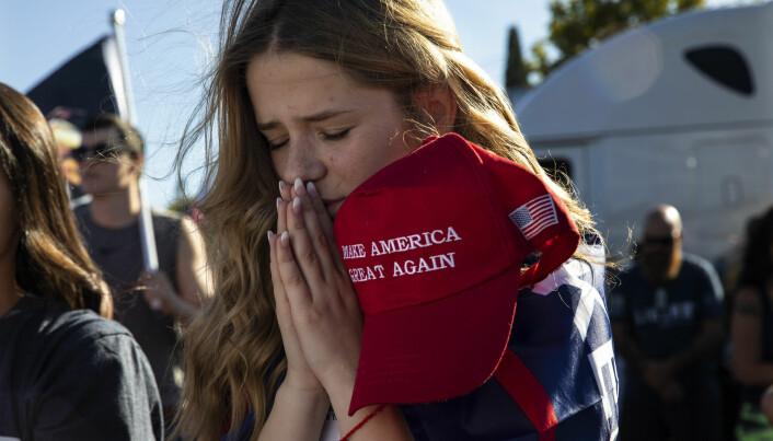 En Trump-tilhenger ber under et valgmøte. Religion spiller en viktig rolle for mange amerikanere og er blitt en stadig viktigere del av amerikansk politikk. Dette er kanskje vanskelig å forstå for folk i det sekulære Norge.