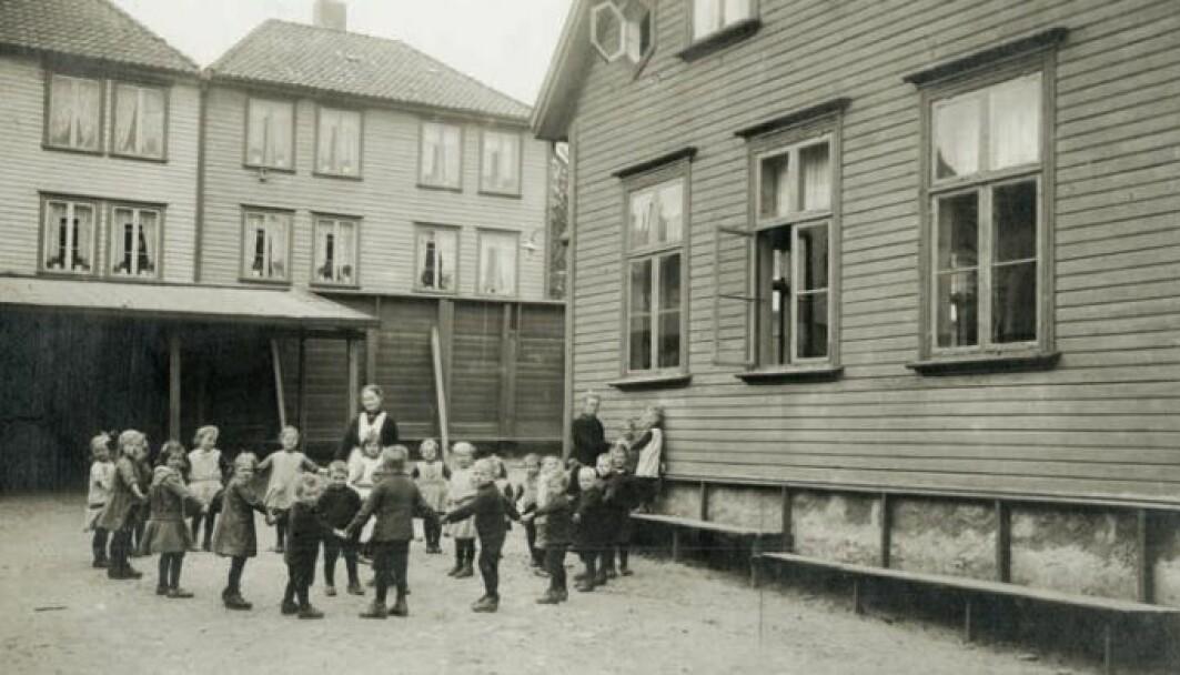 Domkirkens barneasyl 1919: Gårdsrommet er utstyrt med benker og et lite halvtak. - Det ser ut som de leker ringleken. Men dette er et arrangert bildet. Jeg har ingenting i det skriftlige materialet at det var lek sammen med barna. Dette var nok for å gi fotografen et fint motiv, sier Monika Röthle.