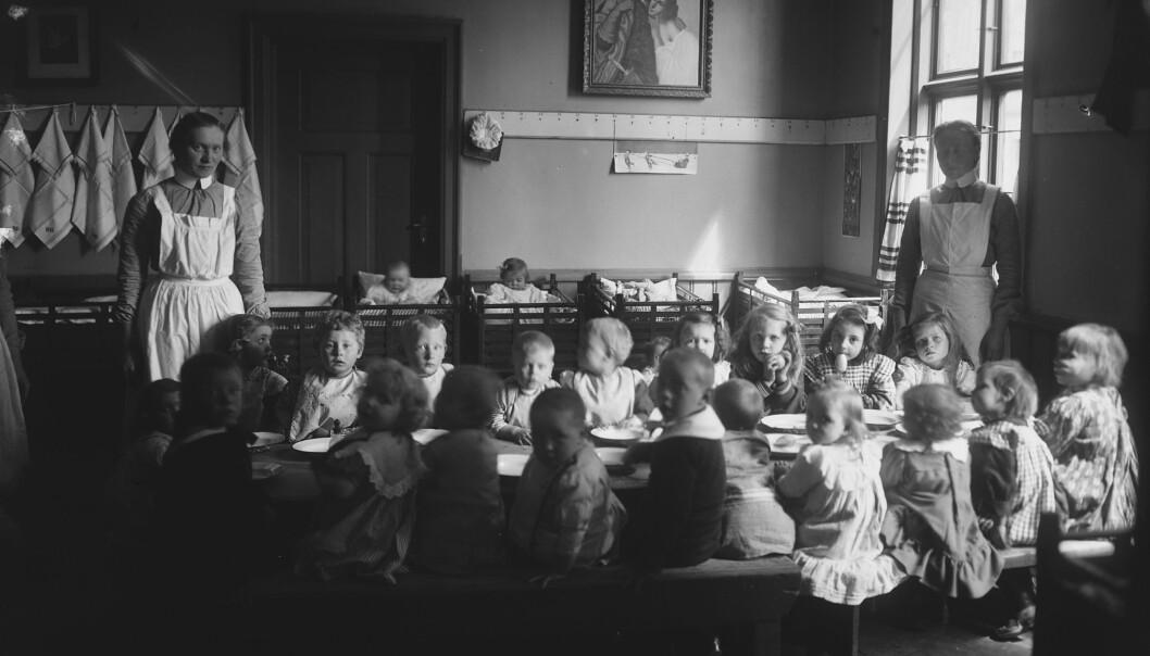 Slik satt de minste barna på rekke og rad rundt formiddagsbordet i barnekrybbene i 1908. Her fra Frelsesarmeen barnekrybbe i Oslo.