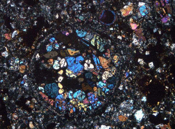 Tynnslip av Oslo-meteoritten. Dei runde kulene vert kalla kondrular, og områda rundt matriks. (Foto: Naturhistorisk museum, UiO)