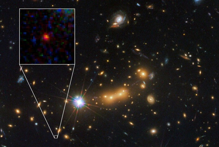 Den ser bare ut som en liten, rød dott på bildet, men det er en hel galakse; langt, langt unna vår egen klode. (Foto: NASA, ESA; M. Postman og D. Coe (Space Telescope Science Institute); samt CLASH-teamet)