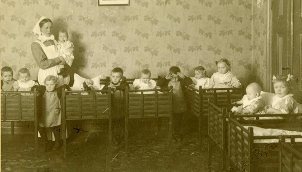 Domkirkens barnekybbe i Stavanger 1919: Bildet viser en menighetssøster og barna i sovestuen. Helt fram til 1970 var denne institusjonen ledet av en diakonisse eller menighetssøster.