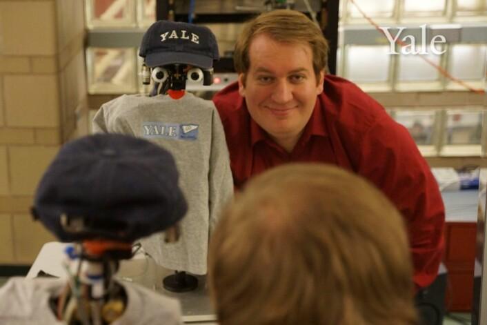 """En av """"pappaene"""" til NICO, Justin Hart poserer med den universitetspatriotisk kledde kjendisroboten. (Foto: Dan Leyzberg/ Yale University)"""