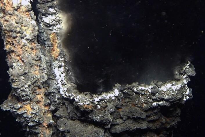 """Svart røyk strømmer ut av en """"pipe"""" i den oppdagede forekomsten """"Lokeryggen"""". Fra jordens indre strømmer kokende vann ut. Når det møter iskald sjø, avsettes verdifule metaller. (Foto: Universitetet i Bergen)"""