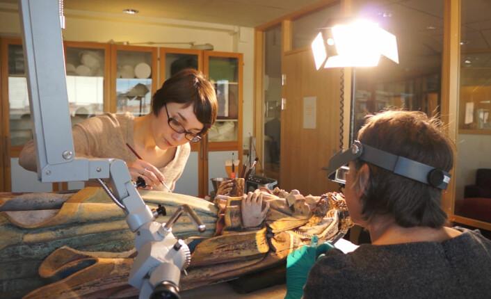 Ingrid Grytdal Matheson (t.v) og Mille Stein arbeider med å restaurere Holdhusmadonnaen. (Foto: Arnfinn Christensen)