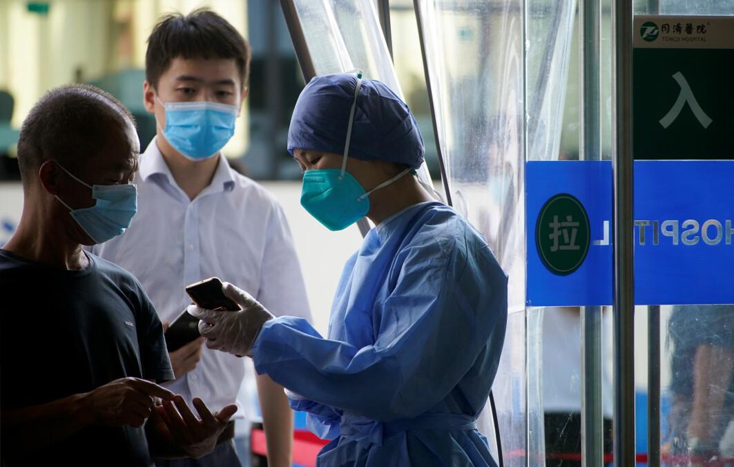 En sykepleier i Wuhan i Kina bruker smarttelefon på jobb. Helsepersonell i Kina har omfavnet WeChat for å kommunisere raskt på tvers av sykehus og landegrenser.