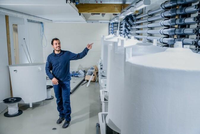 Med RAS-teknologien står norsk oppdrettsnæring foran et stort teknologisk skifte. Vasco Mota forsker på metoder som kan forbedre kvaliteten på vannet som bli resirkulert akvakultursystemet. Her viser han fram deler av et nytt RAS-anlegg under bygging på Havbruksstasjonen i Tromsø.