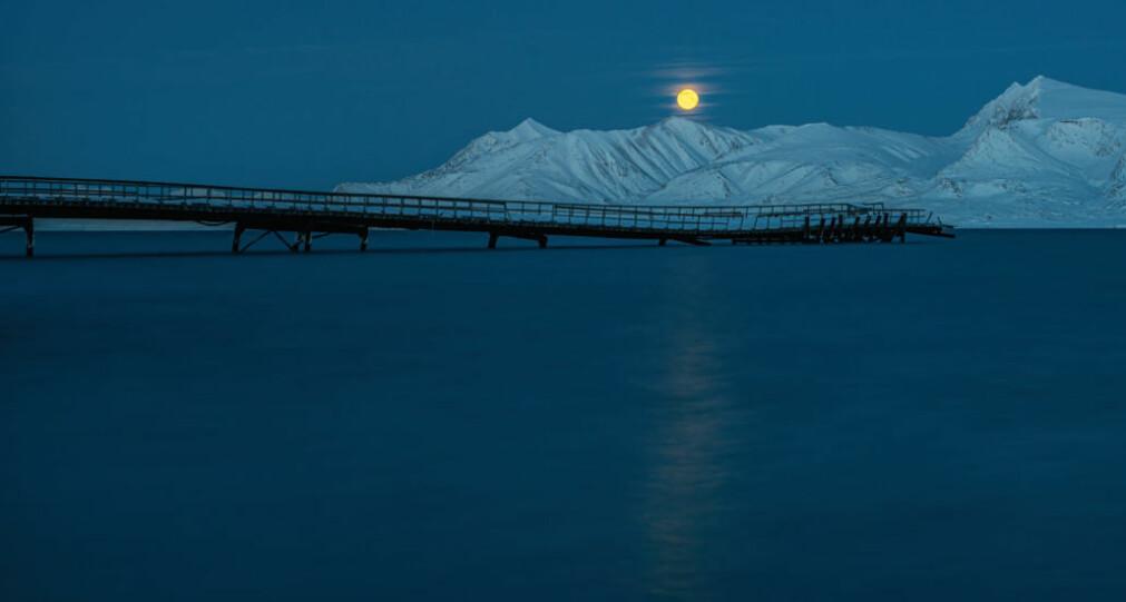 Mørketid med fullmåne i blåtimen, her over «gammelkaia» ved Ny-Ålesund. Kaia er i ferd med å kollapse under påvirkning fra naturkreftene, og ferdsel på den er forbudt.