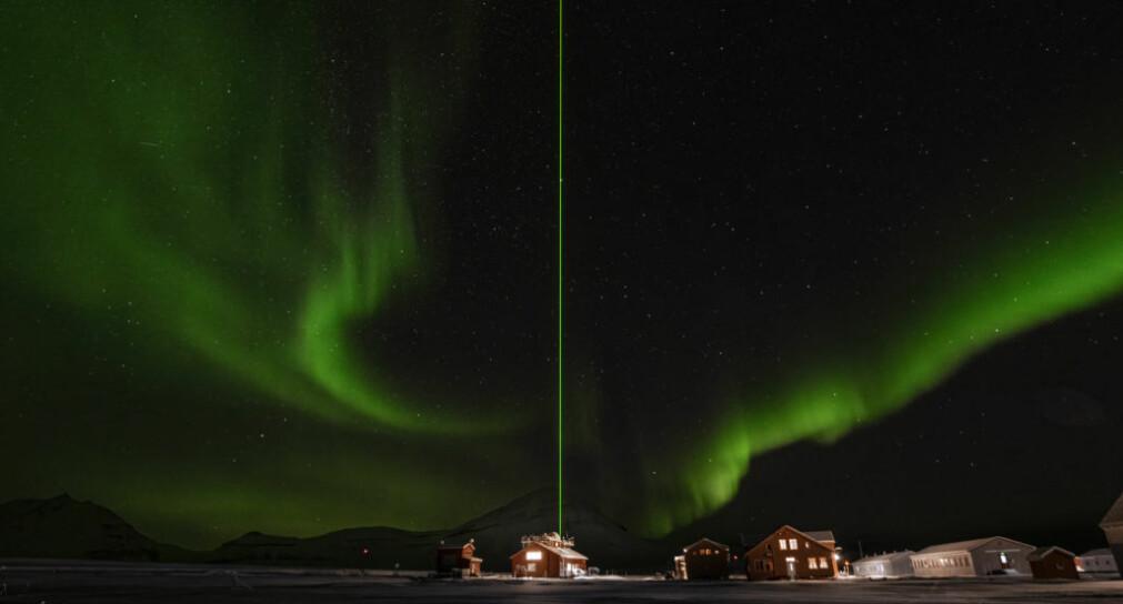 LIDAR-strålen som driftes av tyske Alfred-Wegener-Institute, ser ut til splitte nordlyset over Scheteligfjellet. LIDARen er viktig for å monitorere tynne skyer og små partikler i atmosfæren.